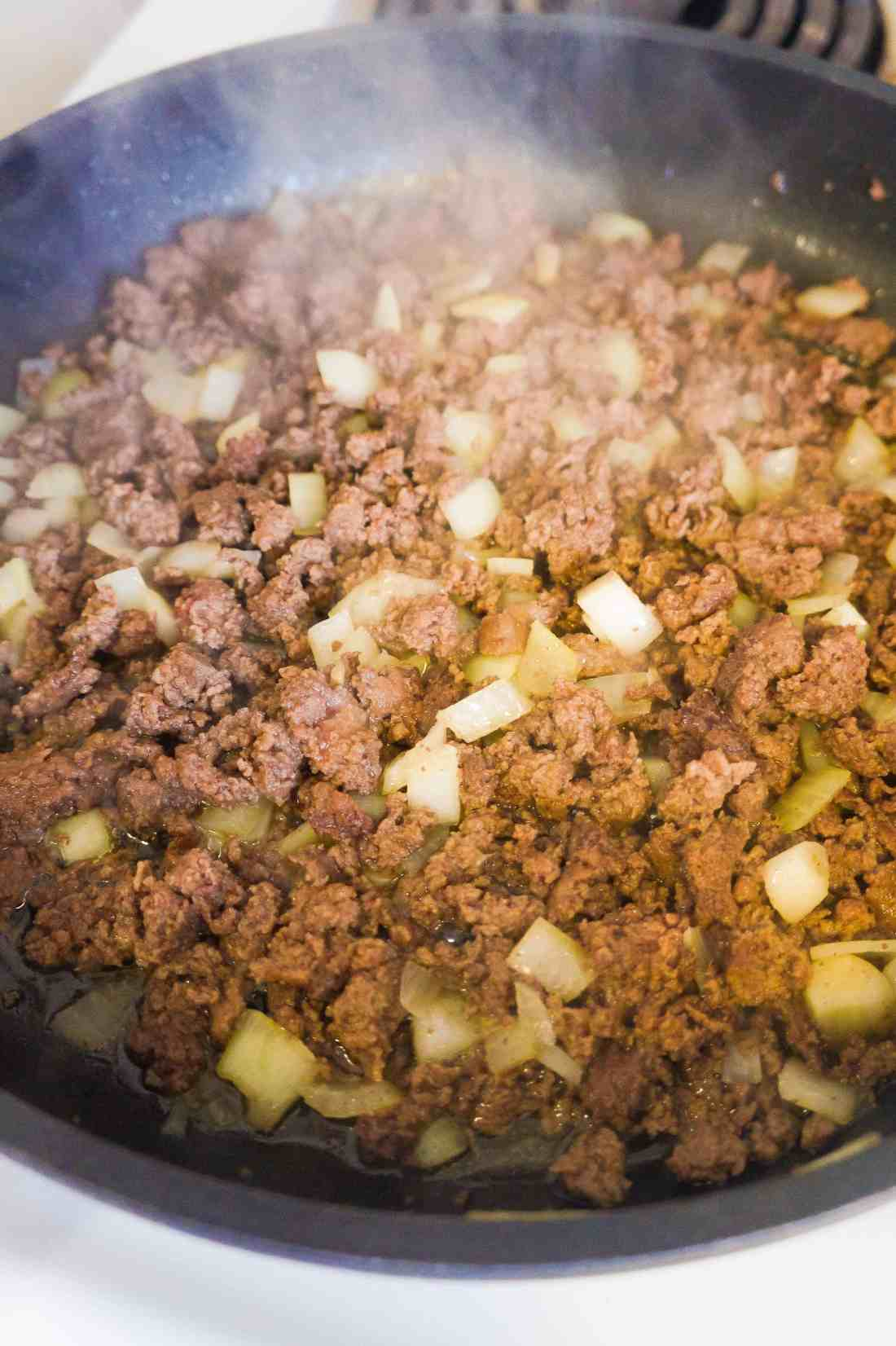 Ground beef and diced onions in frying pan.