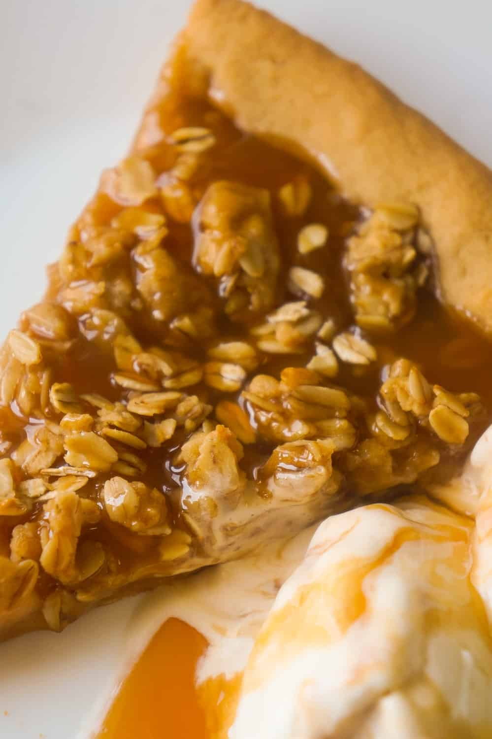 Peanut Butter Apple Pie Cookie Pizza is an easy dessert recipe for peanut butter lovers. A peanut butter cookie crust is topped with apple pie filling, peanut butter oat crumble and drizzled with caramel syrup.
