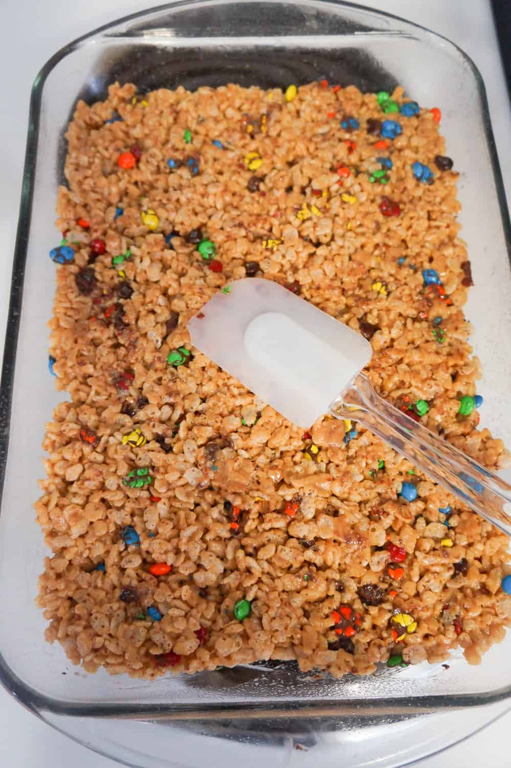 peanut butter rice krispies being pressed into baking dish