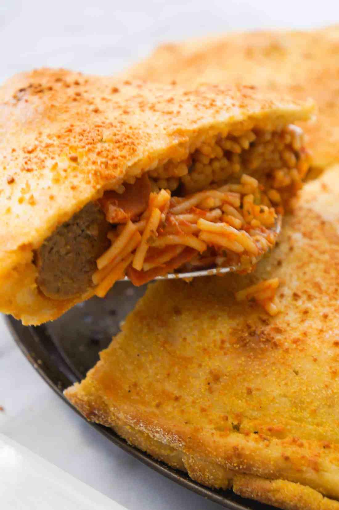 Slice of spaghetti and meatballs stuffed pizza