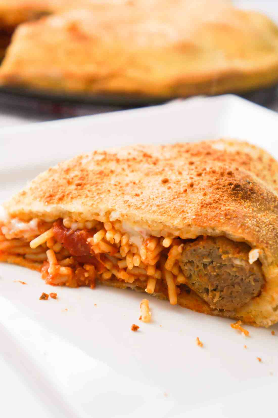 Plate with spaghetti and meatballs pizza slice