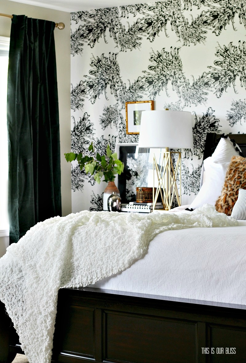 Neutral Master Bedroom with wallpaper accent wall and hunter green velvet curtains