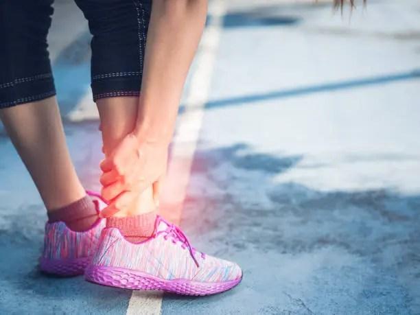 Girl holding ankle spraing injury