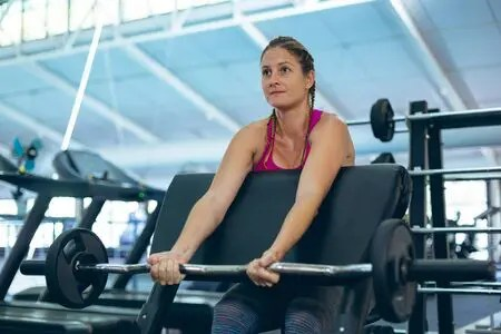 Woman performing preacher curls on bench