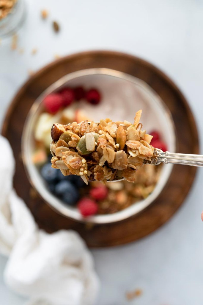 Spoonful of granola over a bowl of yogurt and berries