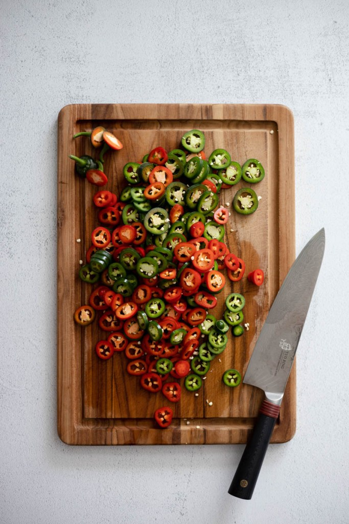 Sliced jalapenos on a cutting board