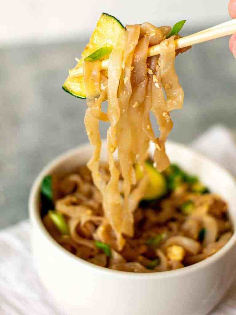 a low carb asian noodle bowl with chopsticks holding up some of the noodleswl with
