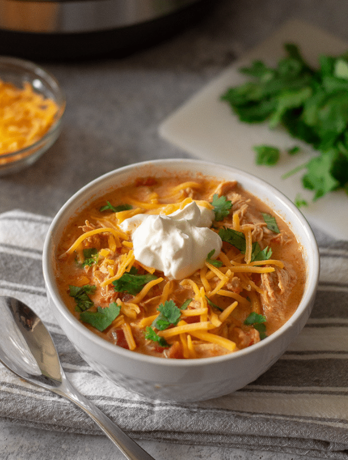 low carb chicken taco soup in a bowl with an instant pot and chopped cilantro in the background