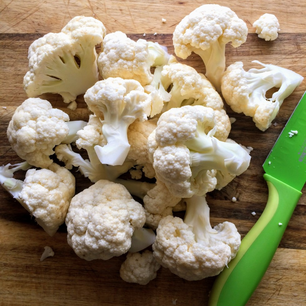 A wooden chopping board, with cauliflower cut into large pieces and a green knife partially pictured