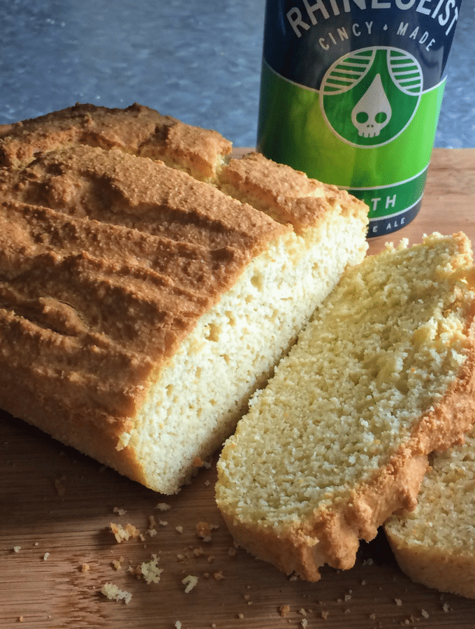Low Carb Beer Bread on a wooden cutting board with a can of beer in the background