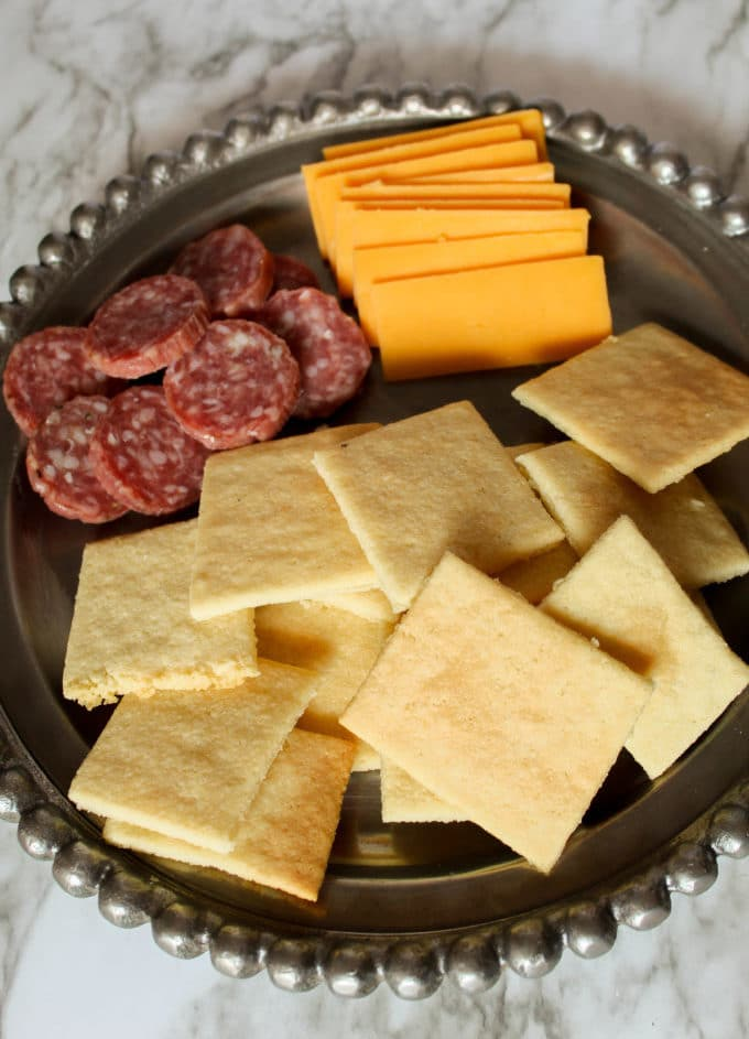 Silver cheese plate with cheddar cheese, salami and keto butter crackers