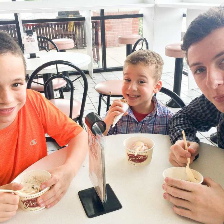 My 3 boys, ages 14, 10 and 3, sitting around a small table eating ice cream