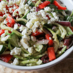 a round, white bowl filled with a salad of zucchini noodles, red peppers, feta cheese, olives, red onion and dressing.