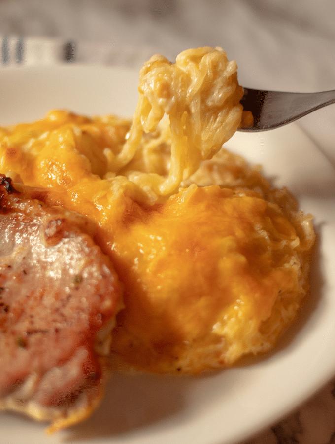 Cheesy spaghetti squash and pork chop casserole on a white plate