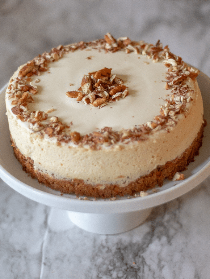 A keto carrot cake cheesecake on a white cakes stand garnished with chopped pecans