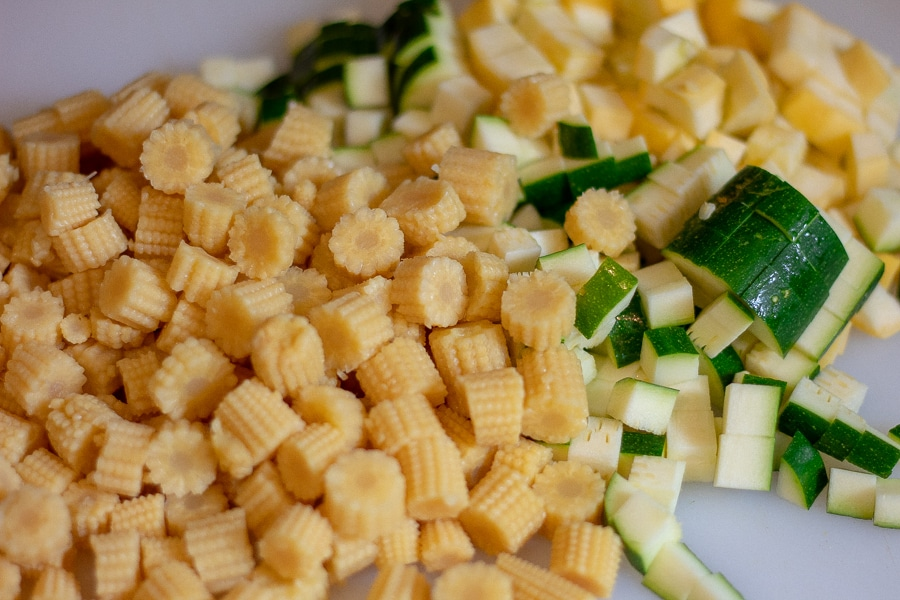 Diced baby corn, zucchini, and yellow squash on a white cutting board in preparation for keto Mexican street corn salad