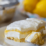 Keto lemon dessert on a white plate with a pile of lemons in the background