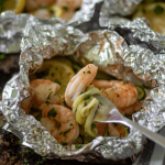 Close up shot of a healthy shrimp foil packet with spiralized zucchini wrapped around a silver fork