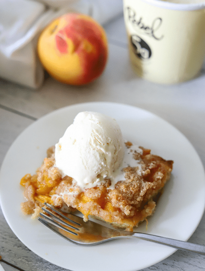 a slice of keto peach cobbler on a white plate topped with vanilla ice cream