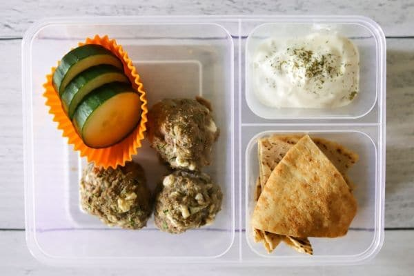 three Greek meatballs, sliced cucumbers, pita chips, and tzatziki sauce in a lunch box