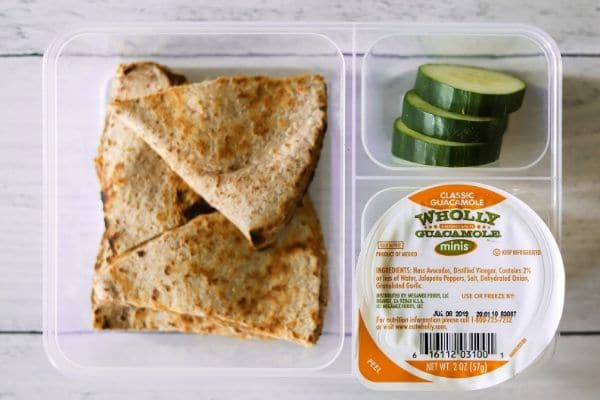 a kids lunch box of a chicken and cheese quesadilla on a low carb tortilla. sliced cucumbers, and guacamole