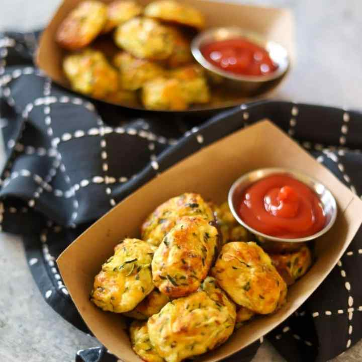 2 containers of zucchini tots with ketchup on the side