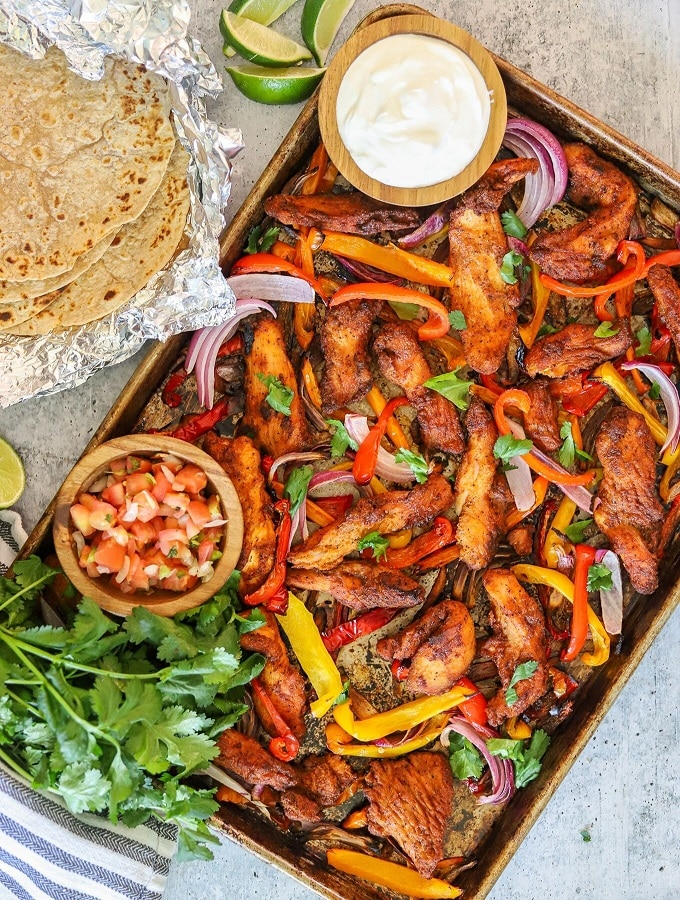 blackened chicken strips, bell peppers, and onion on a sheet pan with fajita toppings on the side