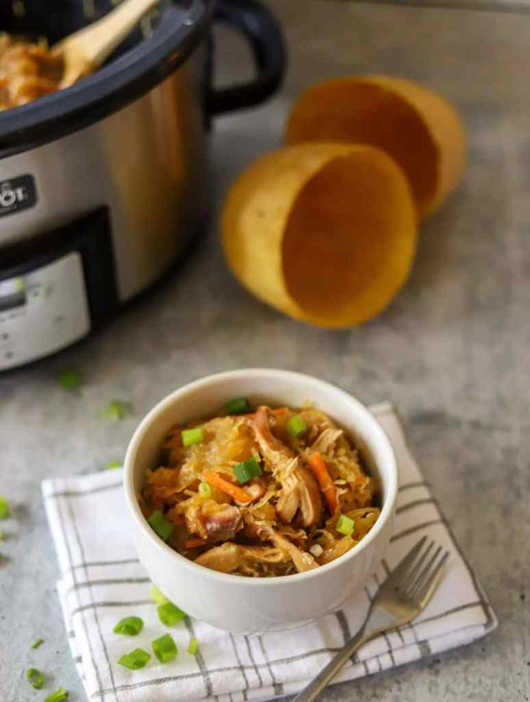 a bowl of spaghetti squash chow main with a slow cooker in the background