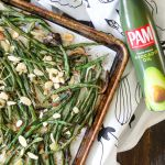Roasted green beans with almonds on a sheet pan with avocado oil spray off to the side.
