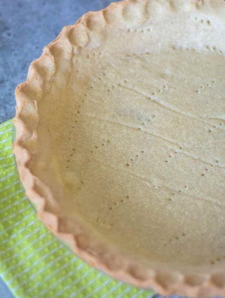 An empty keto friendly pie crust sitting on a green towel