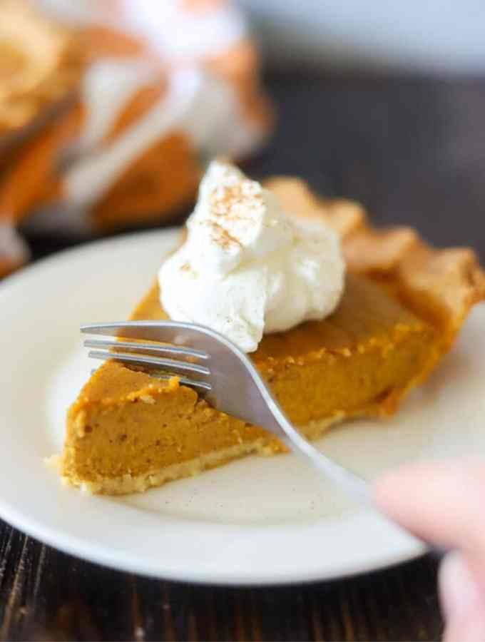 a slice of low carb pumpkin pie topped with homemade whipped cream and cinnamon on a white plate