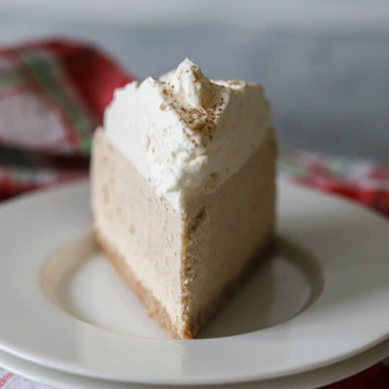 A single slice of low carb eggnog cheesecake on a white plate