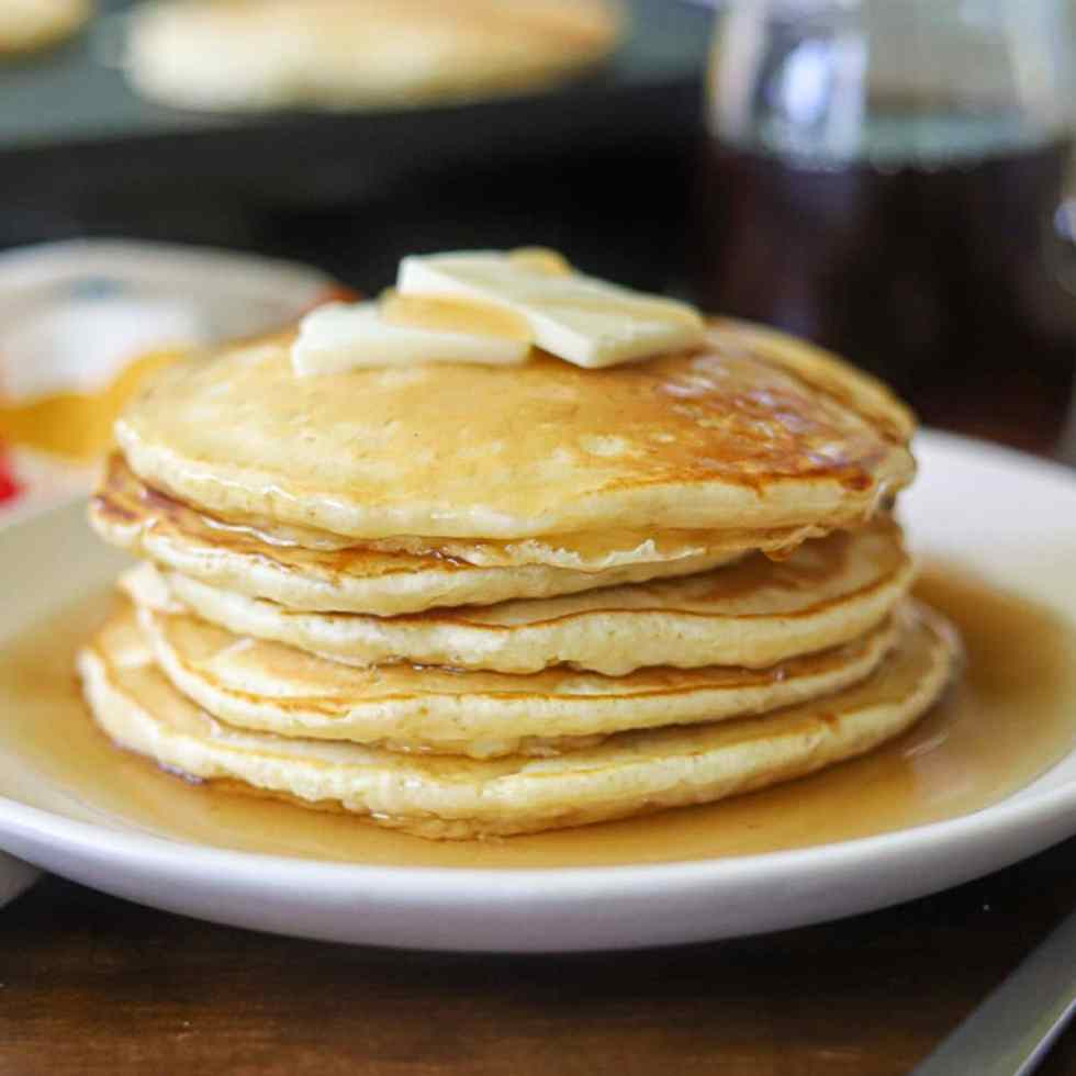 a side view of homemade pancakes stacked up on a plate topped with butter and syrup.