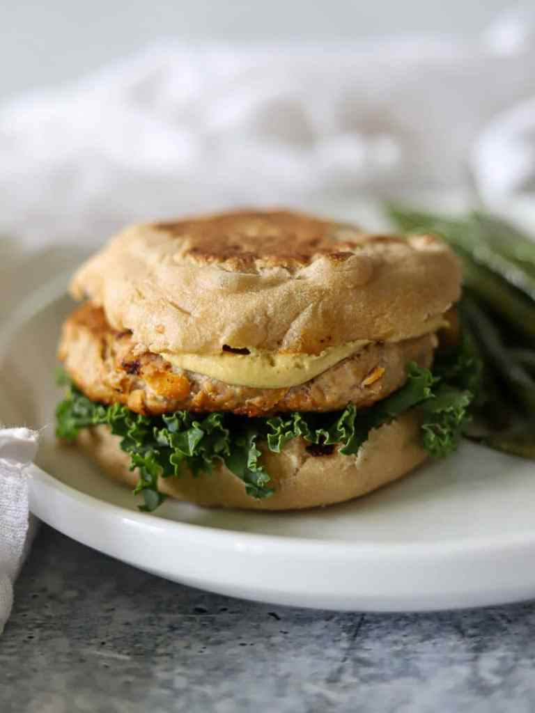 a turkey burger on a wheat english muffins with kale leaves and dijon mustard.