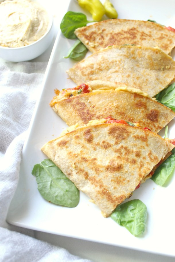 A quick and easy snack or dinner - these Simple Vegan Hummus Quesadillas are packed full of healthy mediterranean flavors. Ready in just 10 minutes! | ThisSavoryVegan.com