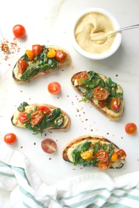Spruce up breakfast or brunch with this Hummus Toast with Wilted Spinach & Tomatoes. A delicious combination of flavors that will take your toast game to new levels   ThisSavoryVegan.com #vegan #brunch