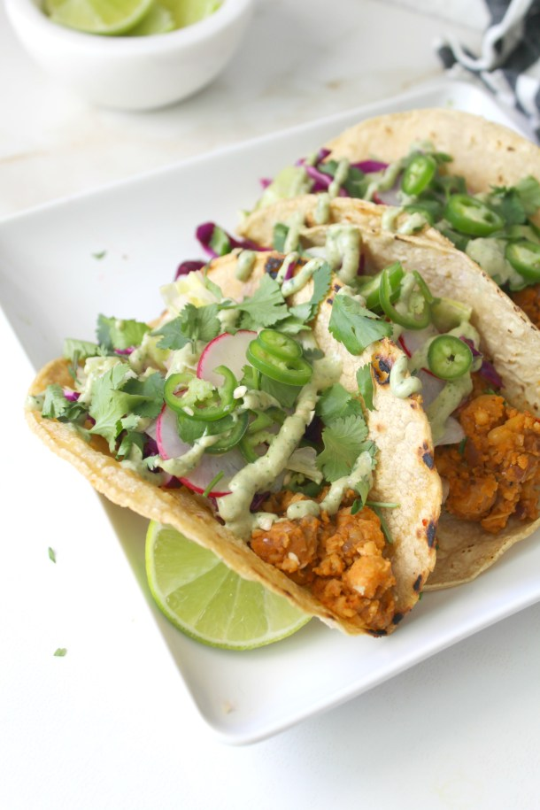 These Smashed Chickpea Tacos with Vegan Jalapeño Cream Sauce are the perfect blend of seasoned chickpeas, fresh slaw and a bit of spice! Taco Tuesday never looked so good | ThisSavoryVegan.com #tacotuesday #vegan