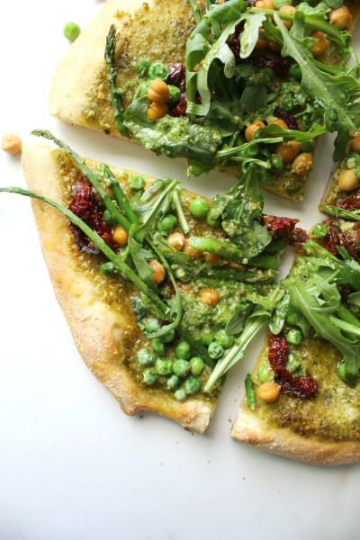 A fresh mix of flavors and veggies comes together with thisSpring Greens Pesto Pizza. A crunchy crust, fresh pesto, sun-dried tomatoes, chickpeas, asparagus, peas and arugula make a light vegan pizza! | ThisSavoryVegan.com #vegan #veganpizza