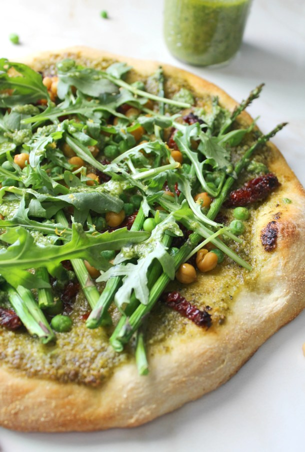 A fresh mix of flavors and veggies comes together with this Spring Greens Pesto Pizza. A crunchy crust, fresh pesto, sun-dried tomatoes, chickpeas, asparagus, peas and arugula make a light vegan pizza! | ThisSavoryVegan.com #vegan #veganpizza