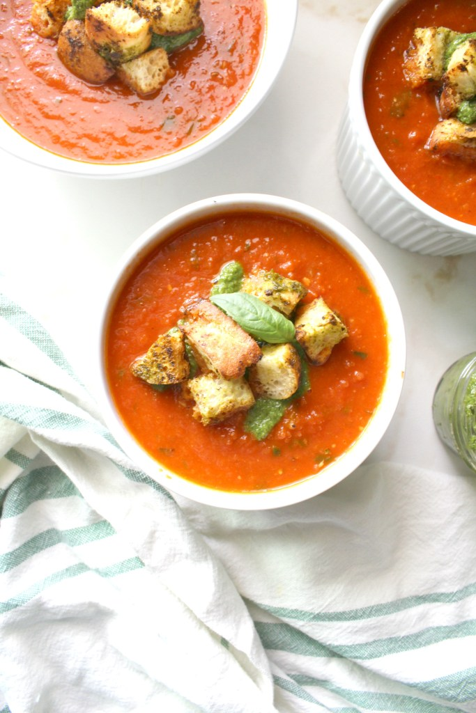 Say so-long to store bought soup with this Tomato Basil Soup with Pesto Ciabatta Croutons. Made simple by using canned tomatoes and made extra delicious with roasted garlic. A quick vegan recipe loaded with fresh flavors | ThisSavoryVegan.com #vegan #soup