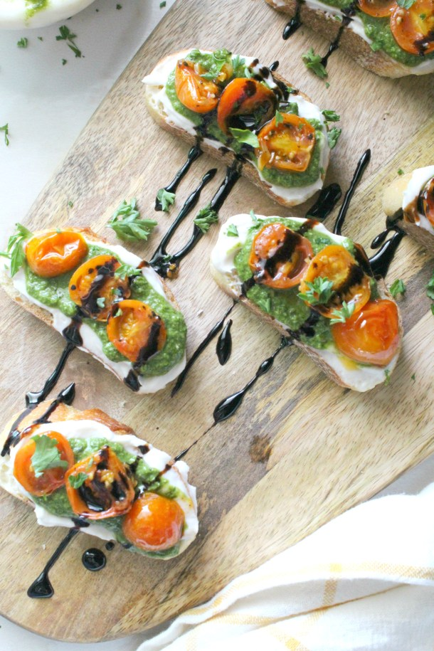 These Vegan Cream Cheese Pesto Crostini are the perfect party appetizer. Smooth cream cheese, vibrant pesto and blistered garlicky tomatoes combine to make the perfect topping for crispy bread | ThisSavoryVegan.com #thissavoryvegan #summer #veganappetizer