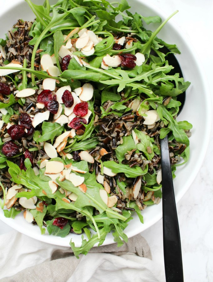 This Wild Rice Arugula Salad is topped with sliced almonds, dried cranberries & a homemade vinaigrette. Perfect winter salad | ThisSavoryVegan.com #thissavoryvegan #vegansalad