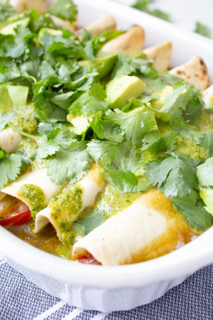 These Creamy Vegan Fajita Enchiladas are loaded with vegan cream cheese, bell peppers & onions, then topped with avocado, cilantro and green sauce | ThisSavoryVegan.com #thissavoryvegan #vegan #veganenchiladas