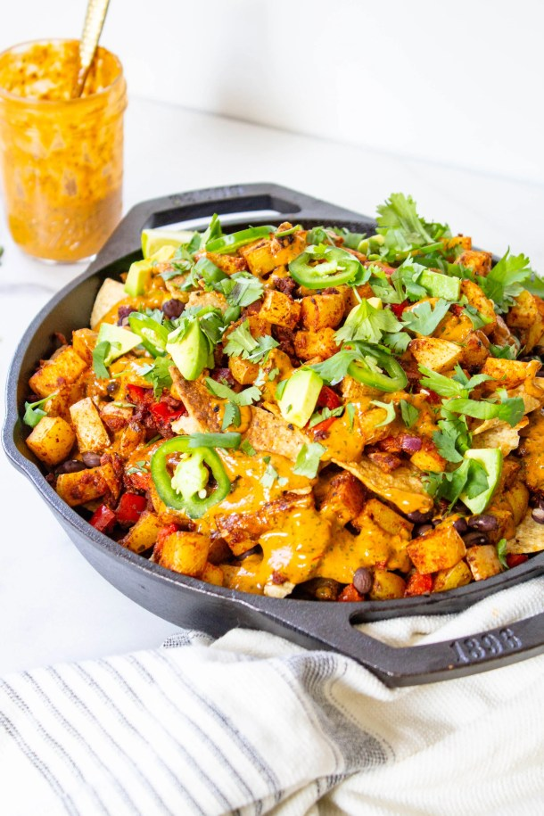 Get ready for your next party with these Potato Soyrizo Skillet Nachos with Chipotle Cilantro Sauce. Loaded with black beans, veggies and vegan sausage | ThisSavoryVegan.com #thissavoryvegan #vegannachos #vegangamedaysnacks