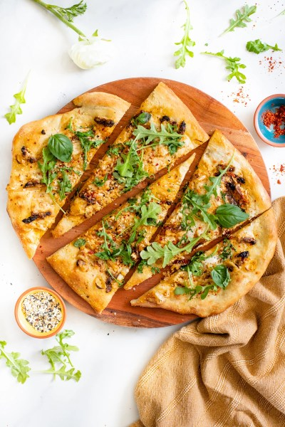 This Everything But the Bagel Vegan Flatbread is made with sun-dried tomatoes, shallots and a white sauce. Topped off with arugula & basil | ThisSavoryVegan.com