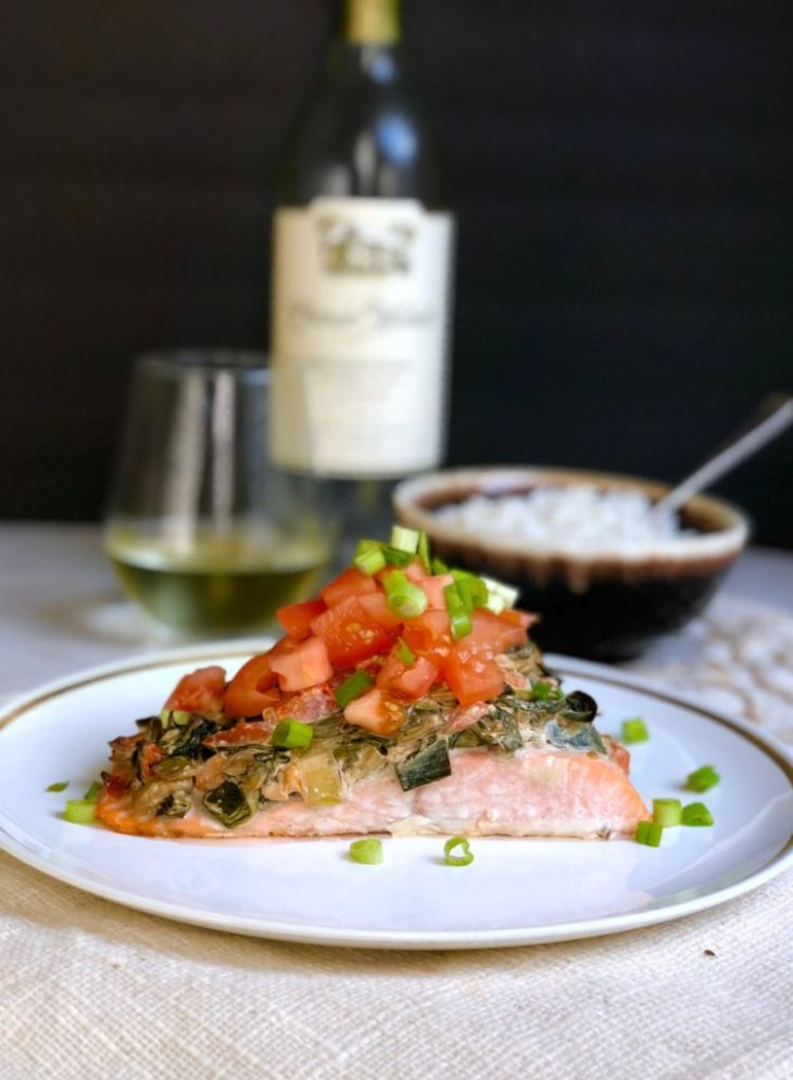 Salmon on plate topped with spinach, leek and white wine sauce with fresh tomatoes and green onions with white wine and rice in background