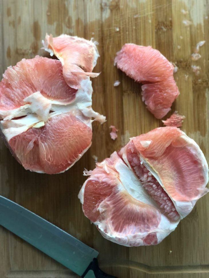 a pomelo being peeled and cut with a knife