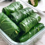 collard green wraps in a container with peanut sauce on the side