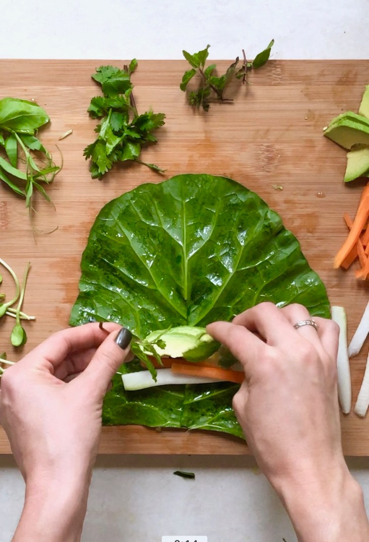 stuffing and wrapping a collard wrap with seasonal vegetables