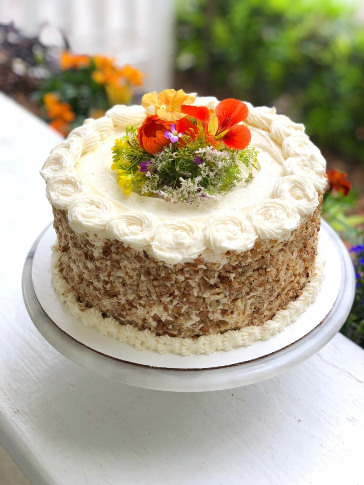carrot cake topped with edible flowers